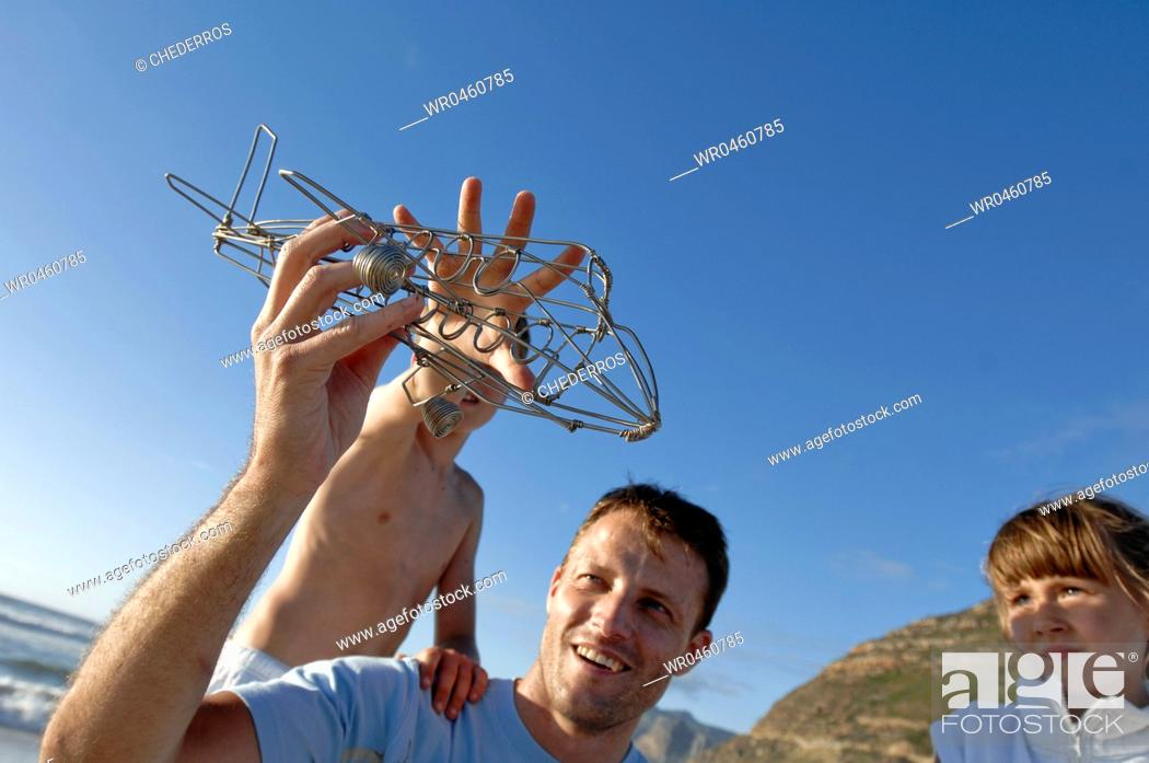 Stock Photo: Mid adult man and his two children playing with a model airplane.