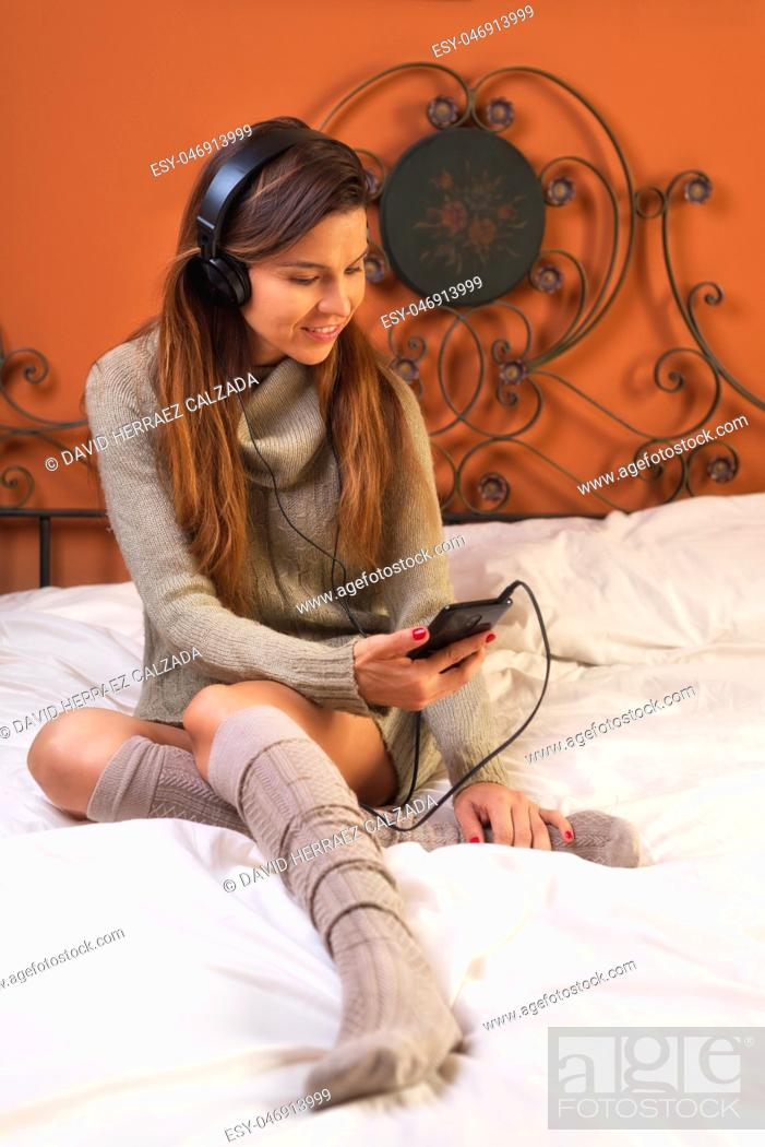 Stock Photo: Young Woman Listening Music with Headphones on the Bed .