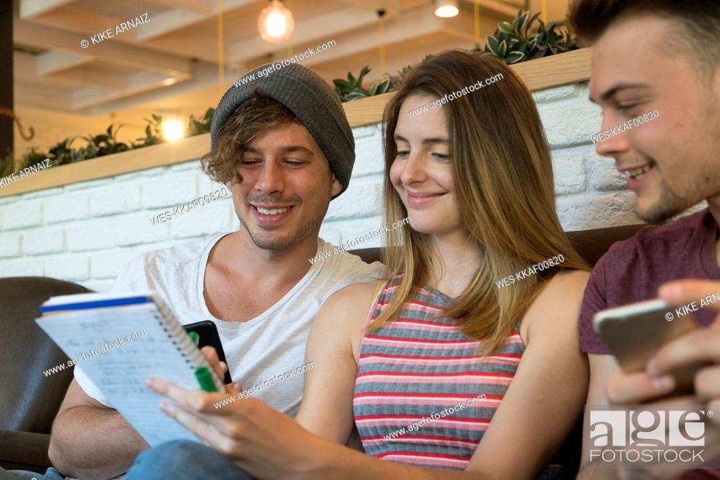 Stock Photo: Three friends with notepad and cell phones in a cafe.