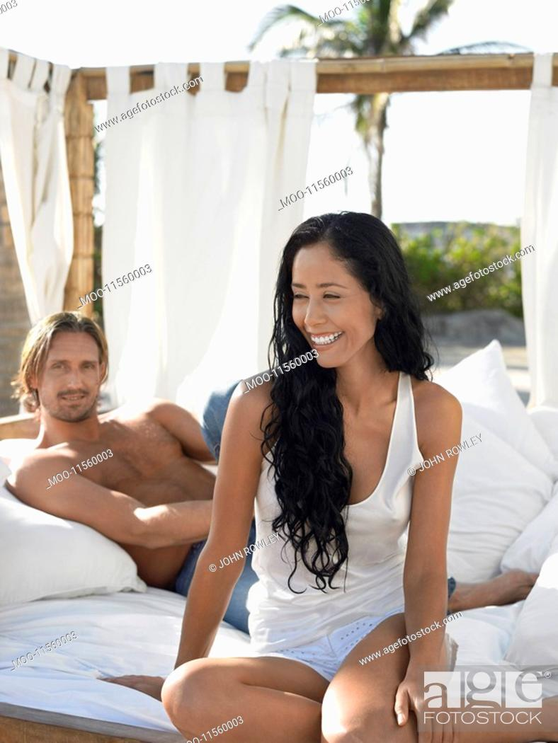 Stock Photo: Couple on bed on beach.