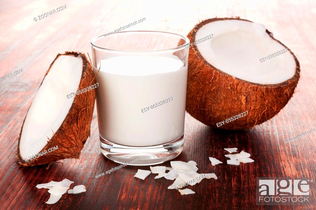 Stock Photo: Healthy coconut milk in glass with shredded coconut with coconut flakes on wooden table.