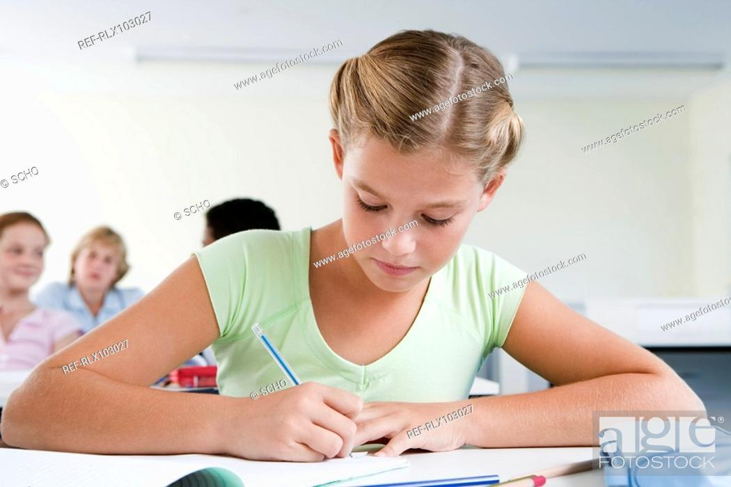 Stock Photo: School girl 10-13 writing in classroom, concentrating.