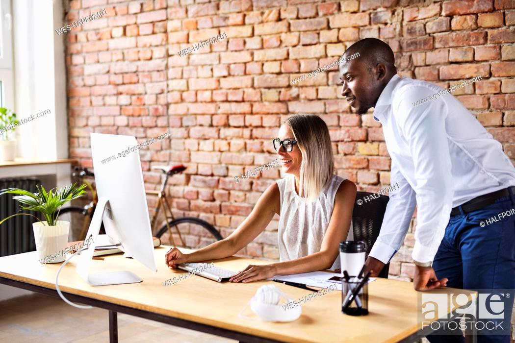 Stock Photo: Two colleagues working together at desk in office.