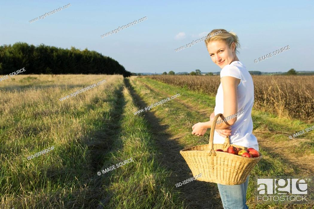 Stock Photo: Woman in field with basket.