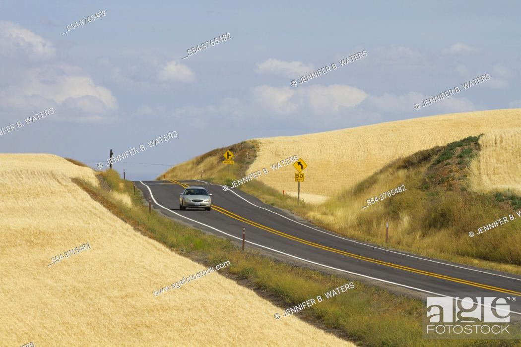 Stock Photo: Car driving on a rural highway in the Palouse farming area of eastern Washington State, USA.