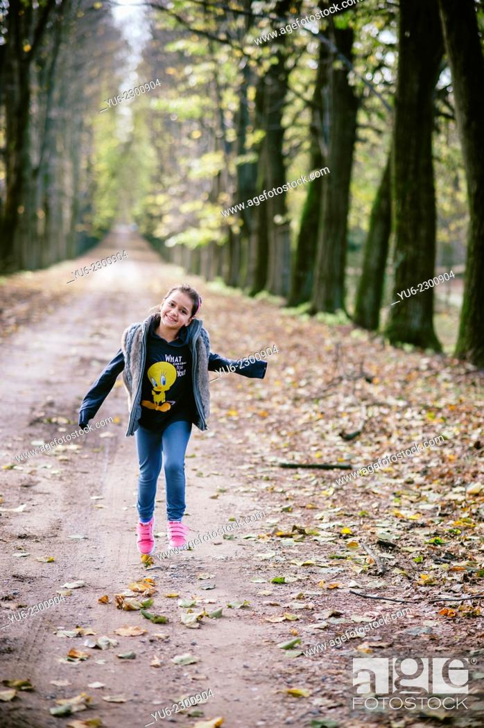 Stock Photo: Girl runs along an avenue of lime trees in autumn.