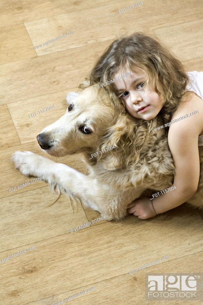 Stock Photo: A young girl hugging a dog.