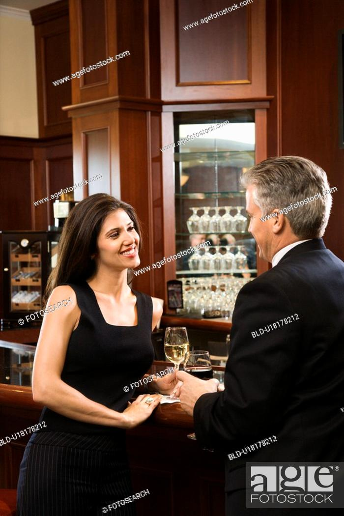 Stock Photo: Female and male standing at bar talking.