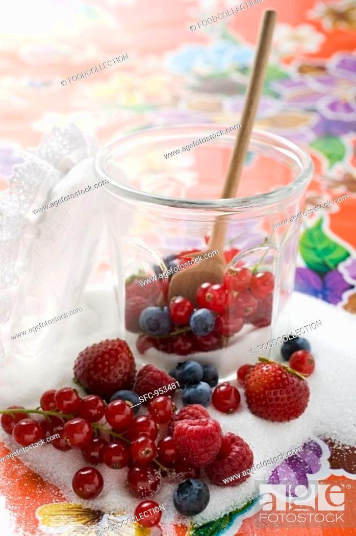 Stock Photo: Fresh berries in jam jar with sugar and wooden spoon.
