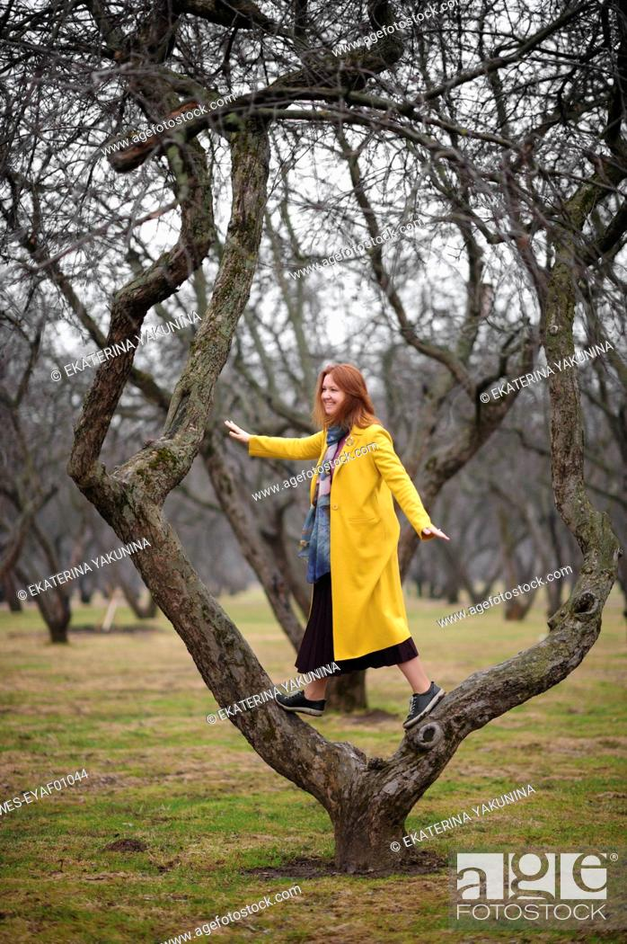 Photo de stock: Full length of woman in yellow coat standing on bare tree at park.