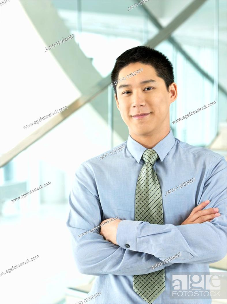 Stock Photo: Confident Businessman standing arms crossed.