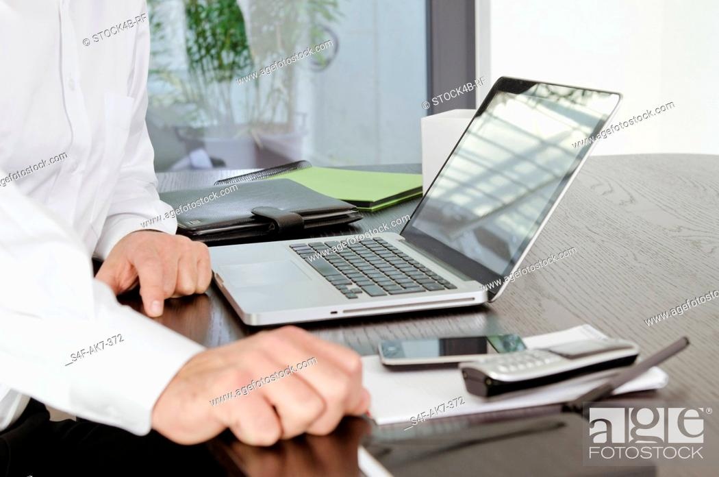 Stock Photo: Businessman sitting at desk with laptop.