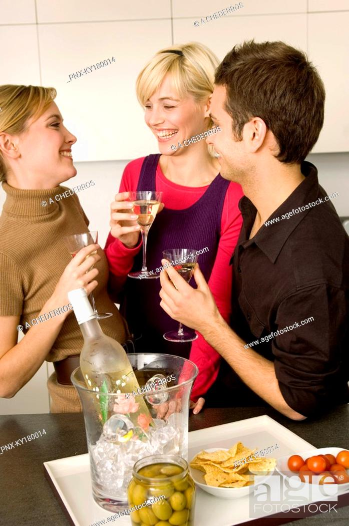 Stock Photo: Two young women and a young man holding martini glasses.