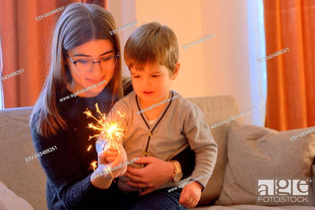 Stock Photo: Little boy and teen girl holding a sparkler inside of house.