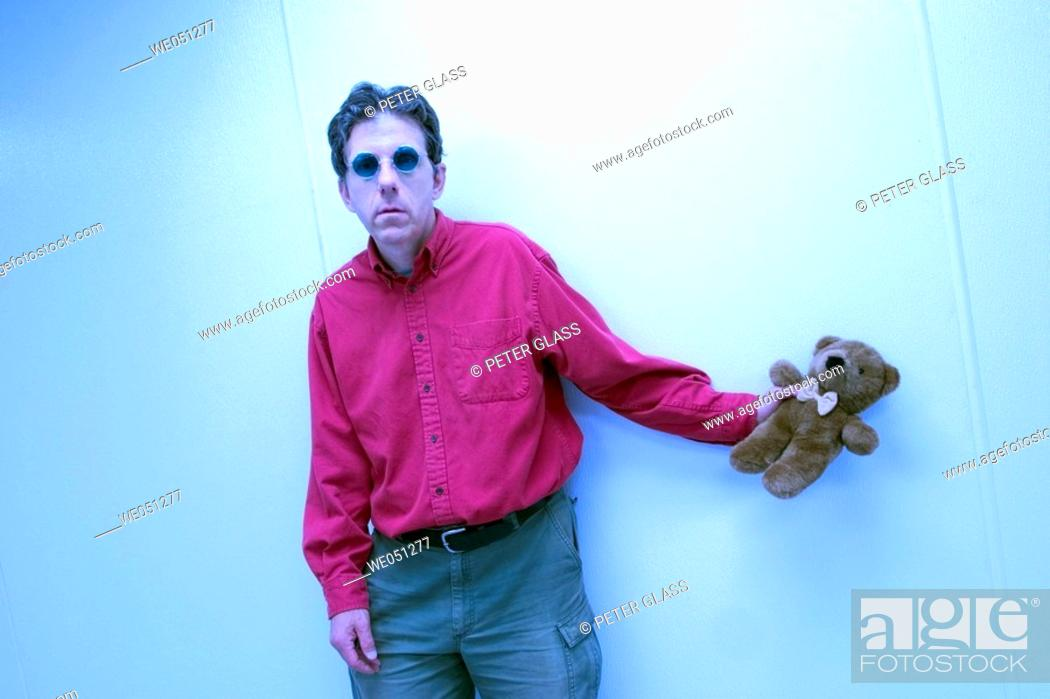 Stock Photo: Middle-age man, wearing sunglasses and standing by a wall, holding a stuffed teddy bear.