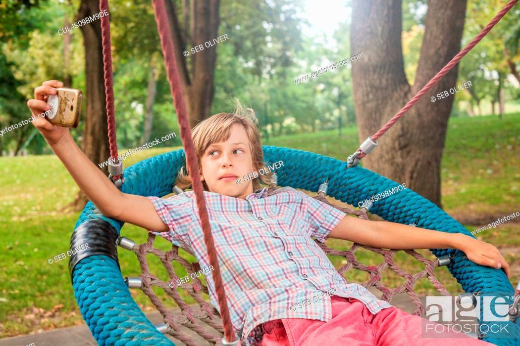 Stock Photo: Boy taking selfie on web swing.