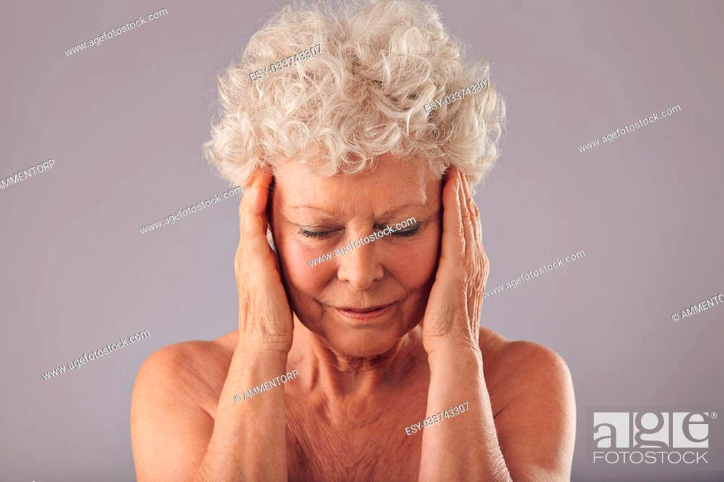 Stock Photo: Close-up studio portrait of mature woman in her 70s touching her face against grey background. Old woman examining her skin condition.