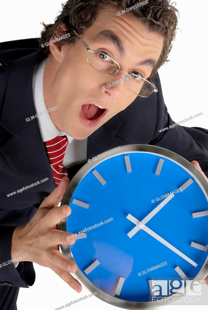 Stock Photo: Portrait of a businessman holding a clock.