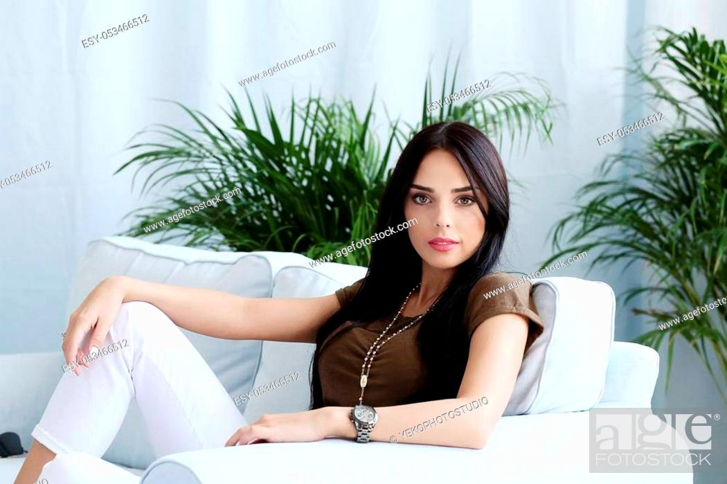 Stock Photo: Beautiful woman sitting on a sofa at home.