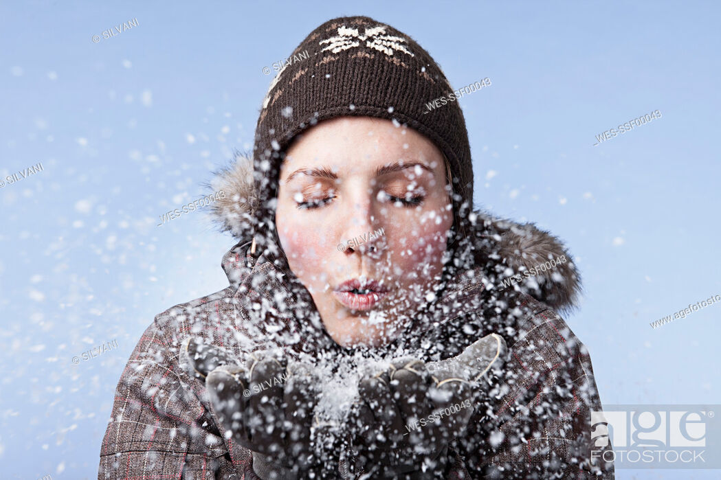 Stock Photo: Young woman blowing snow, close-up.