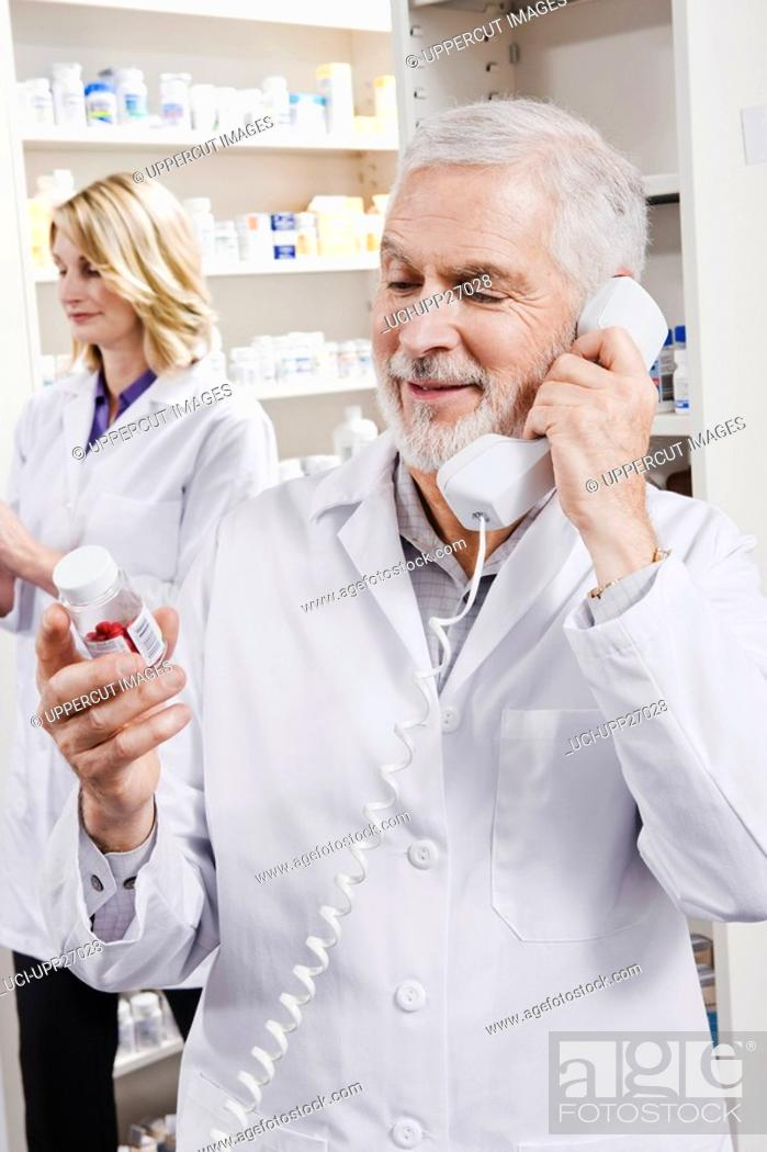 Stock Photo: Pharmacist holding pill bottle and talking on telephone.