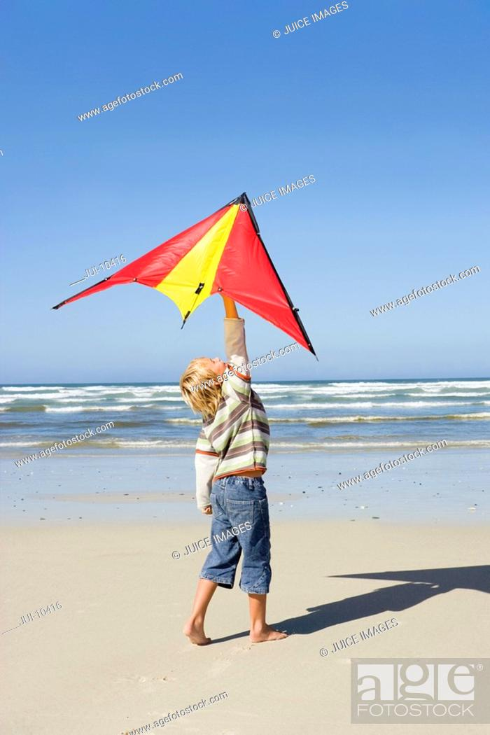 Stock Photo: Boy 6-8 holding up kite on beach, side view.