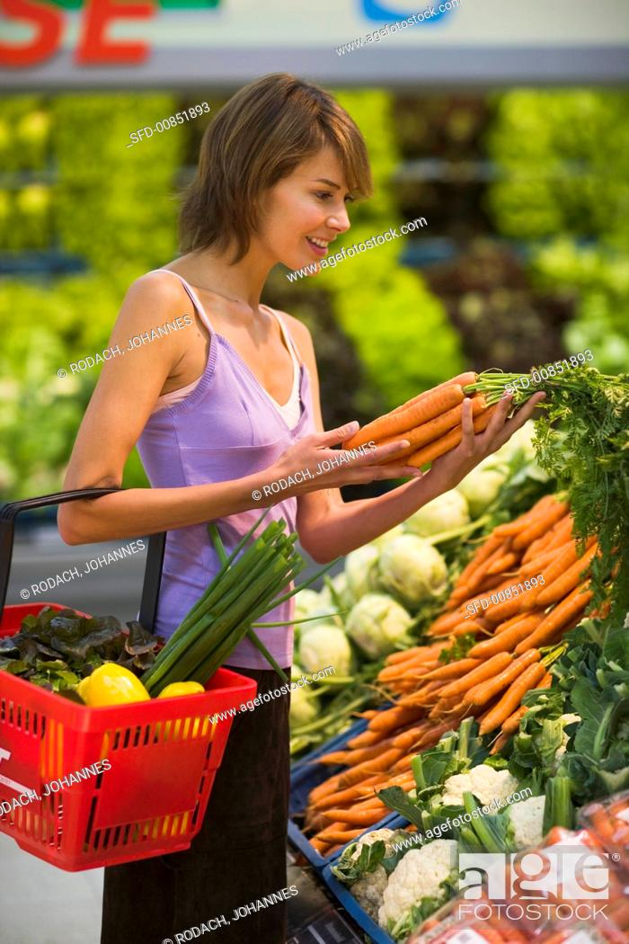 Stock Photo: Young woman at the vegetable counter in a supermarket.