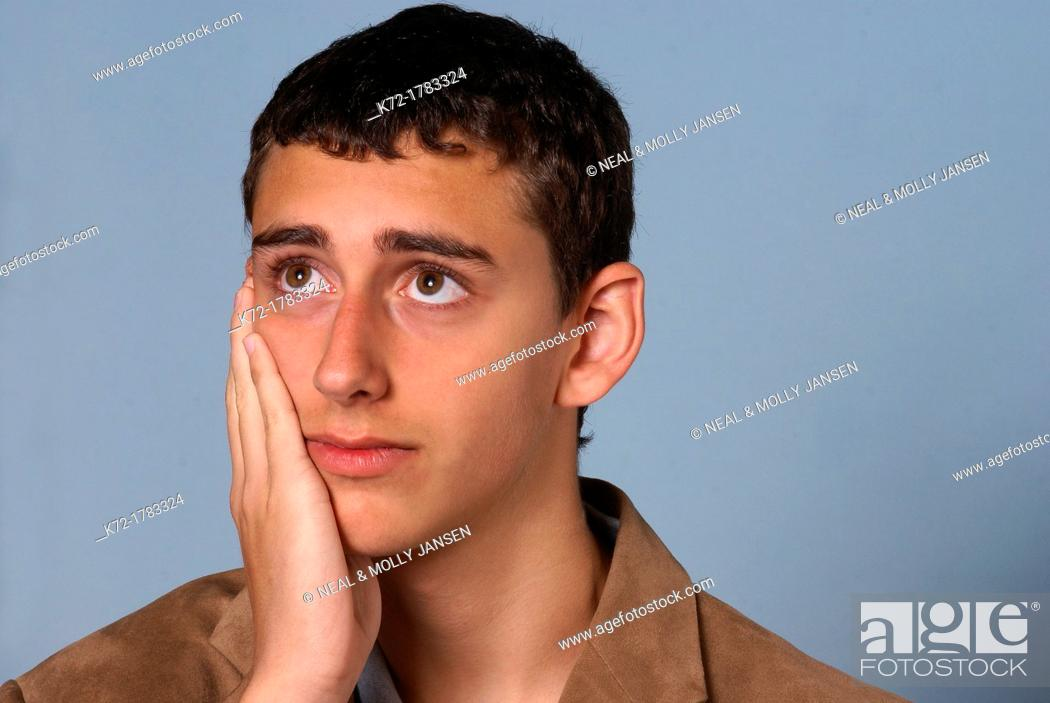 Stock Photo: Worried look on face of young teenage man.