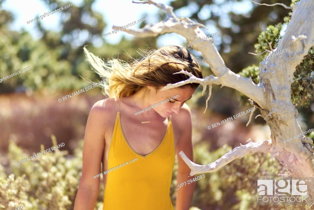 Stock Photo: young woman behind withered tree in nature. Dutch ethnicity. At holiday destination Chrissi Island, Crete, Greece.