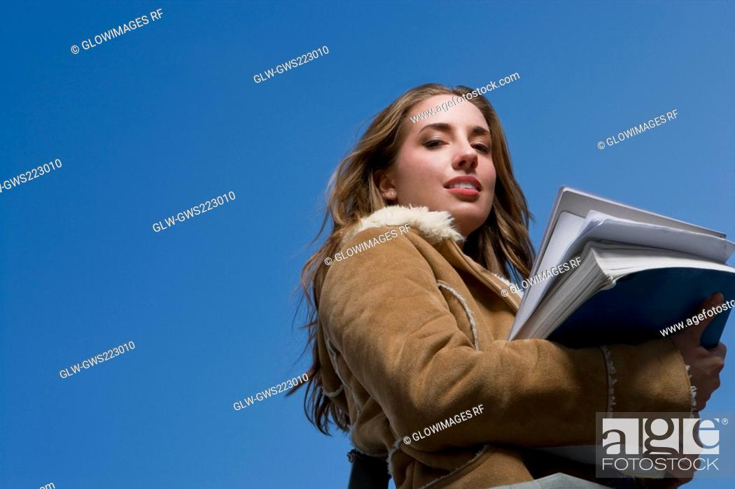 Stock Photo: Low angle view of a young woman holding textbooks.