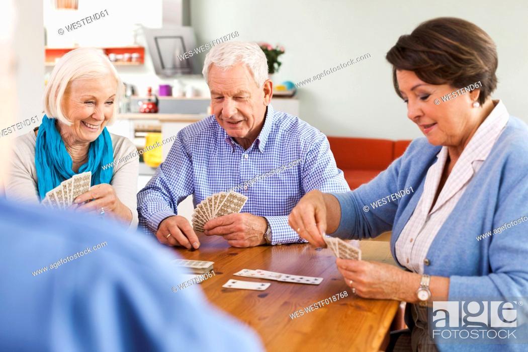 Stock Photo: Germany, Leipzig, Senior men and women playing cards, smiling.