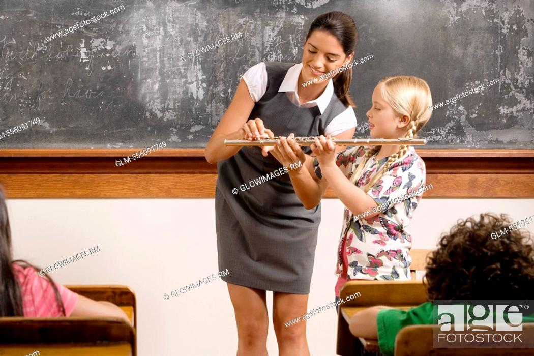 Stock Photo Teacher Helping A Schoolgirl Playing A Flute In A Classroom