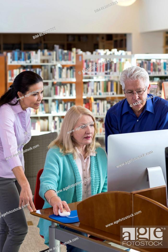 Stock Photo: Older people using computer in library.
