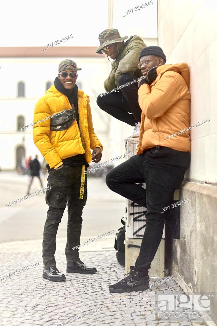 Stock Photo: three stylish male friends together at street, wearing urban fashion trend outfit, in city Munich, Germany.