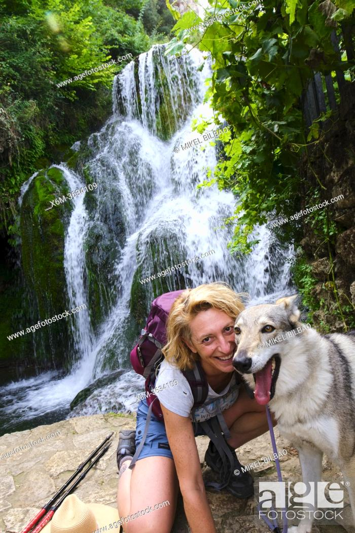 Stock Photo: Hiker mature young woman with a dog and waterfall. Tobera, Frias town, Burgos, Castile and Leon, Spain.