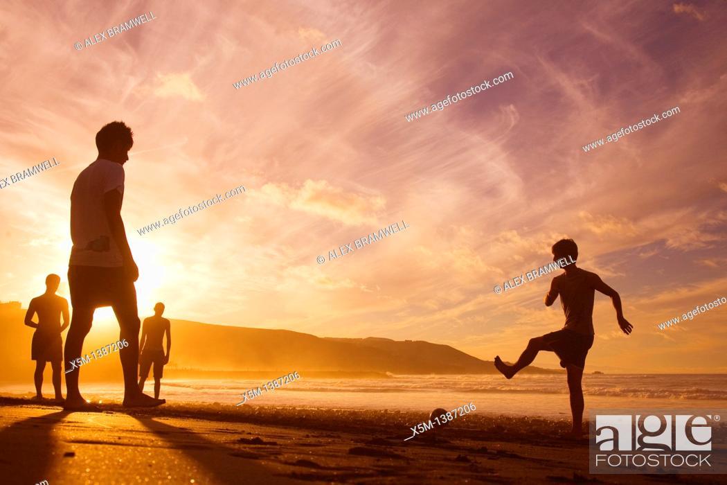 Stock Photo: Boys playing football on the beach at sunset  Las Canteras beach in Las Palmas de Gran Canaria.
