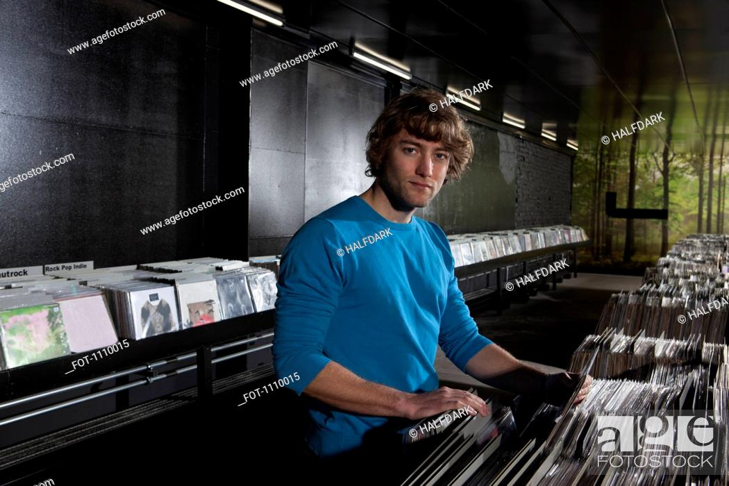 Stock Photo: A young man in a record shop, looking at camera.