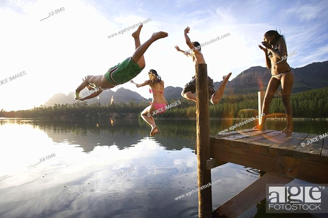 Stock Photo: Four young adults diving from jetty into lake at sunset, side view lens flare.