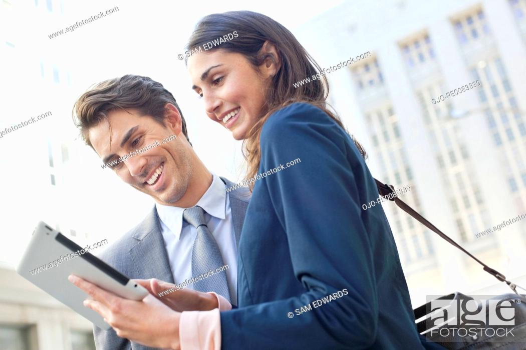 Stock Photo: Businessman and businesswoman using digital tablet.
