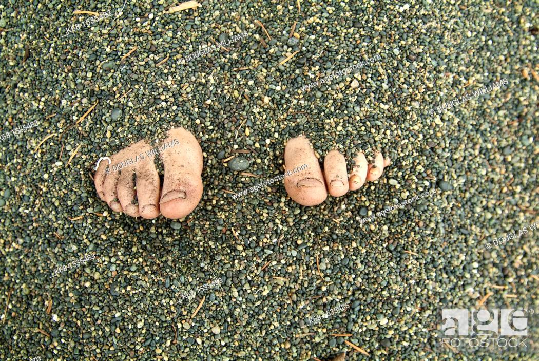 Stock Photo: Toes showing from feet buried in sand.