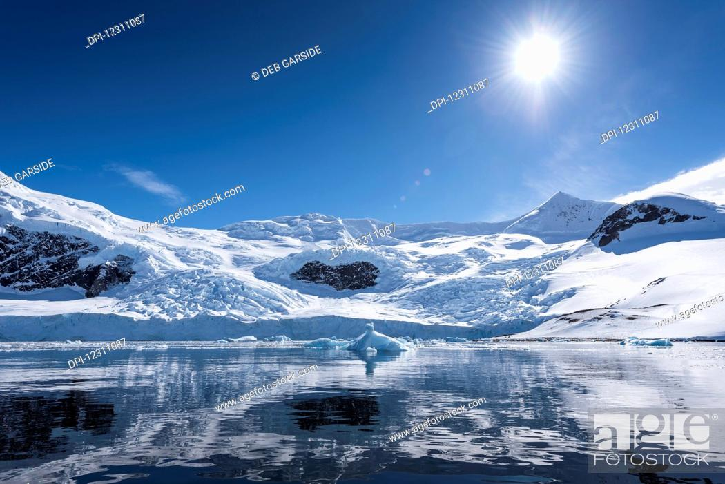 Imagen: Bright sun and snow on the mountains reflected in the water of Neko Harbour; Antarctica.