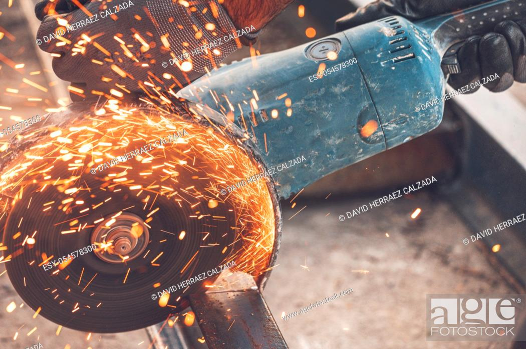 Stock Photo: Construction worker using Angle Grinder cutting Metal at construction site .