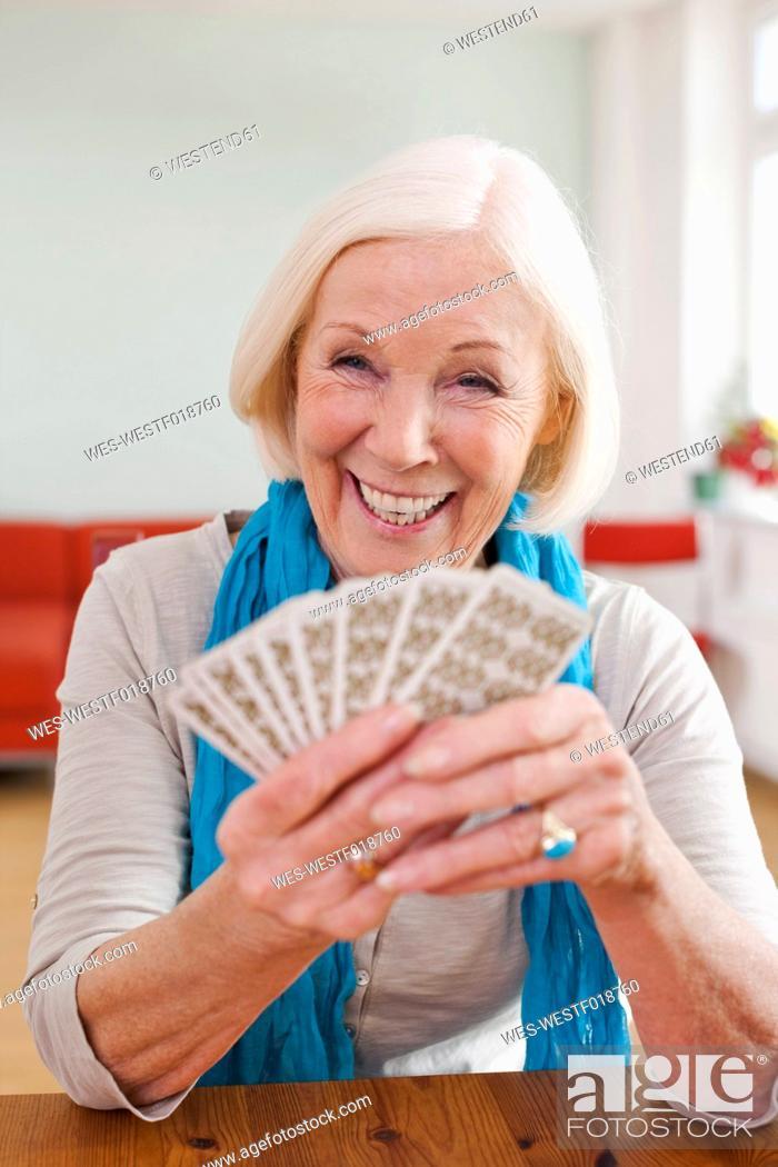 Stock Photo: Germany, Leipzig, Senior woman playing cards, smiling.