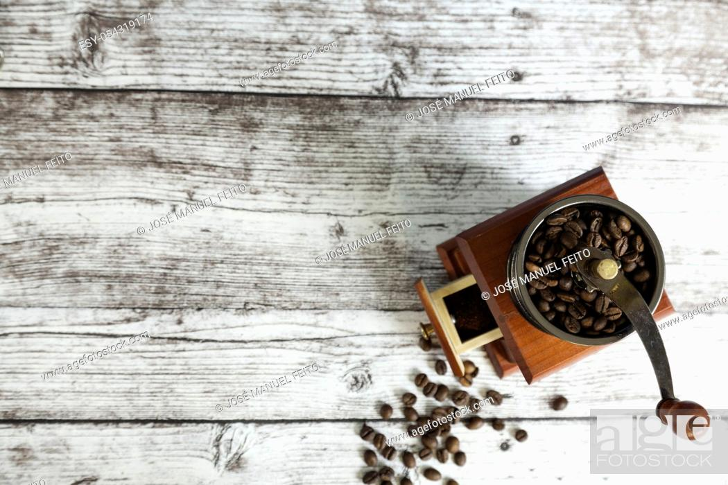 Stock Photo: coffee grinder with coffee grains on wooden table from above. Top view.