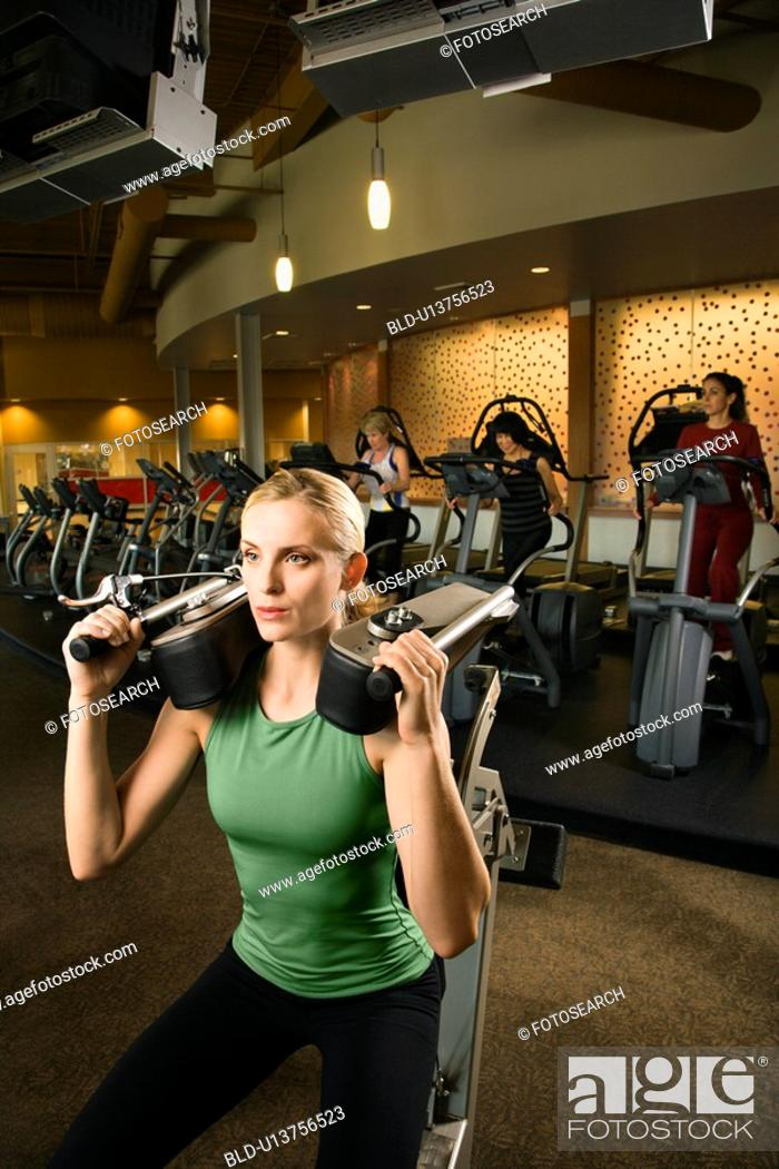 Stock Photo: Female using exercise equipment at gym.