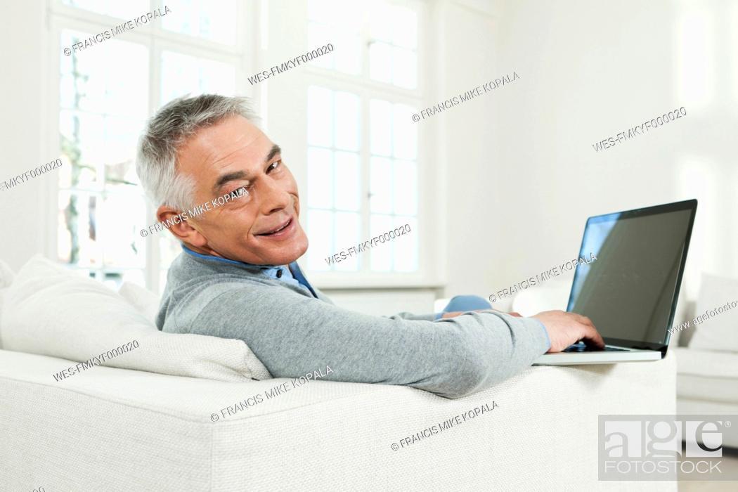 Stock Photo: Germany, Berlin, Senior man using laptop, portrait.