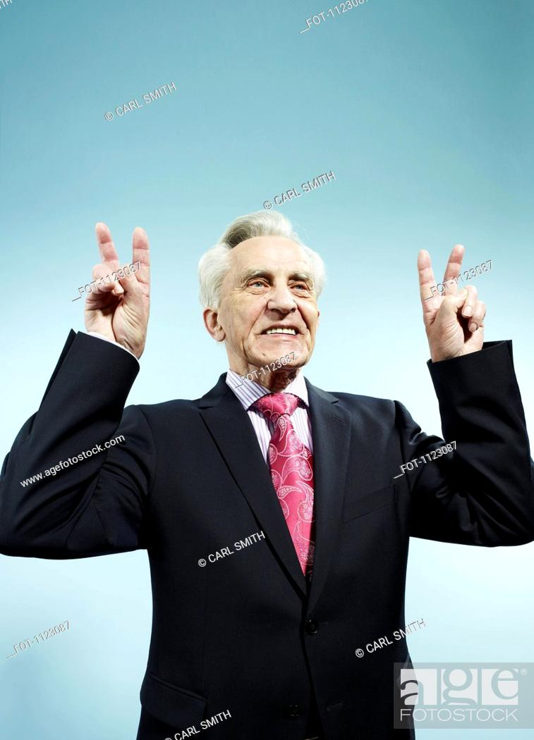 Stock Photo: A senior man with both hands raised making peace signs.