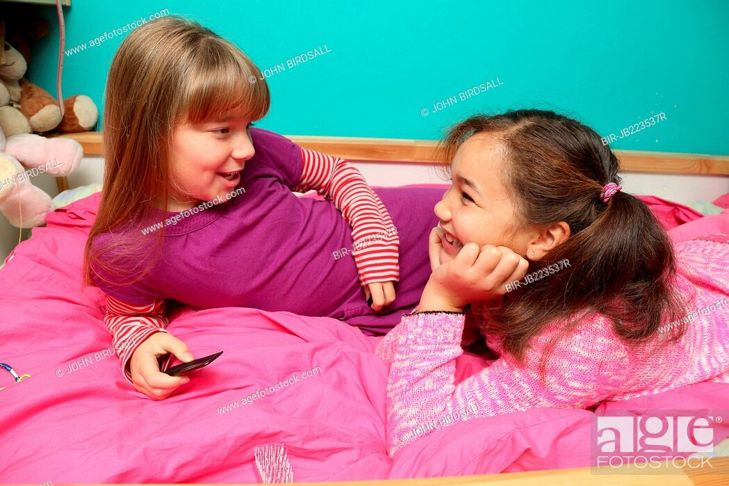 Stock Photo: Young girls chatting in bedroom.
