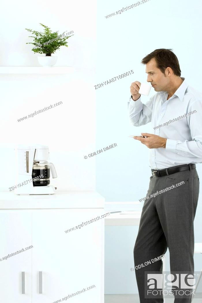 Stock Photo: Man standing by coffee maker, taking a sip of coffee, holding saucer.