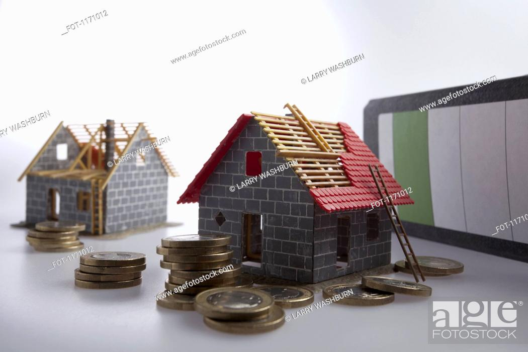 Stock Photo: Two partially constructed models of a house with piles of European Union coins around them.
